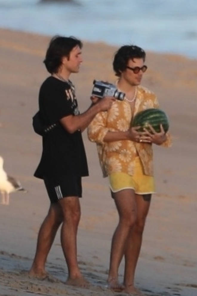 Harry Styles holds a watermelon on Malibu beach whilst shooting a music video