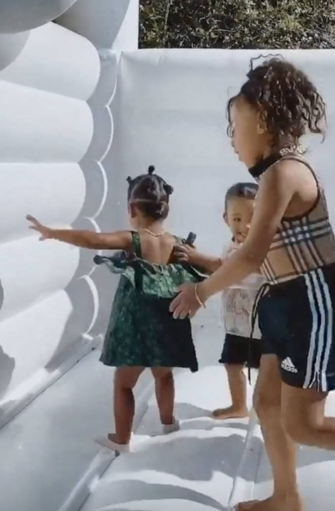 True Thompson and North and Chicago West can be seen on a bouncy castle together