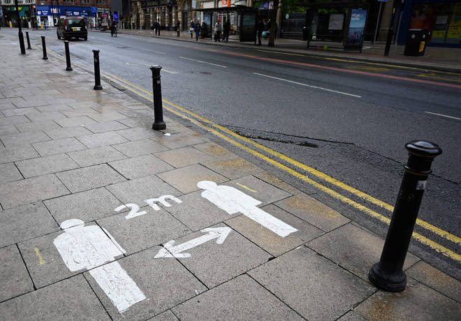 Markings on the pavement advises pedestrians to stay two meters (2M) apart