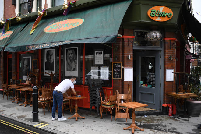 Pub worker cleans tables ahead of the business reopening