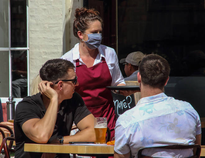 A waitress wearing a face mask as a preventive measure...