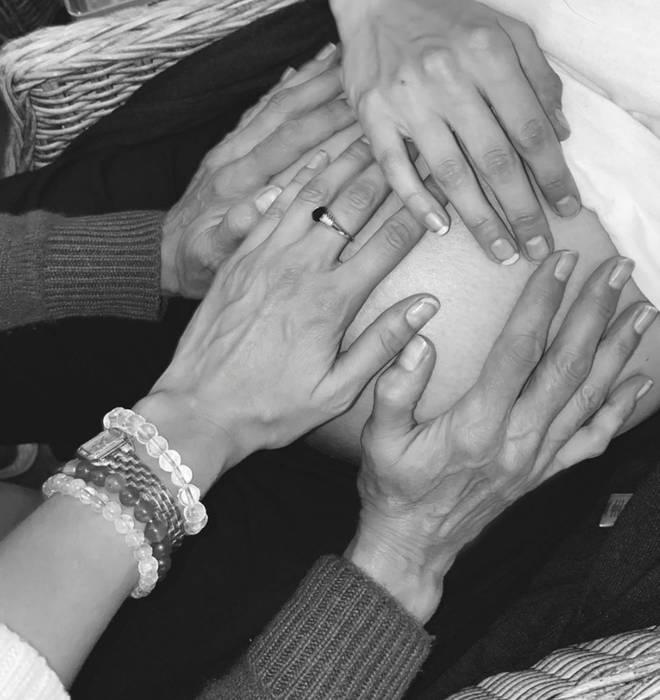 Yolanda and Bella Hadid with their hands on Gigi's stomach