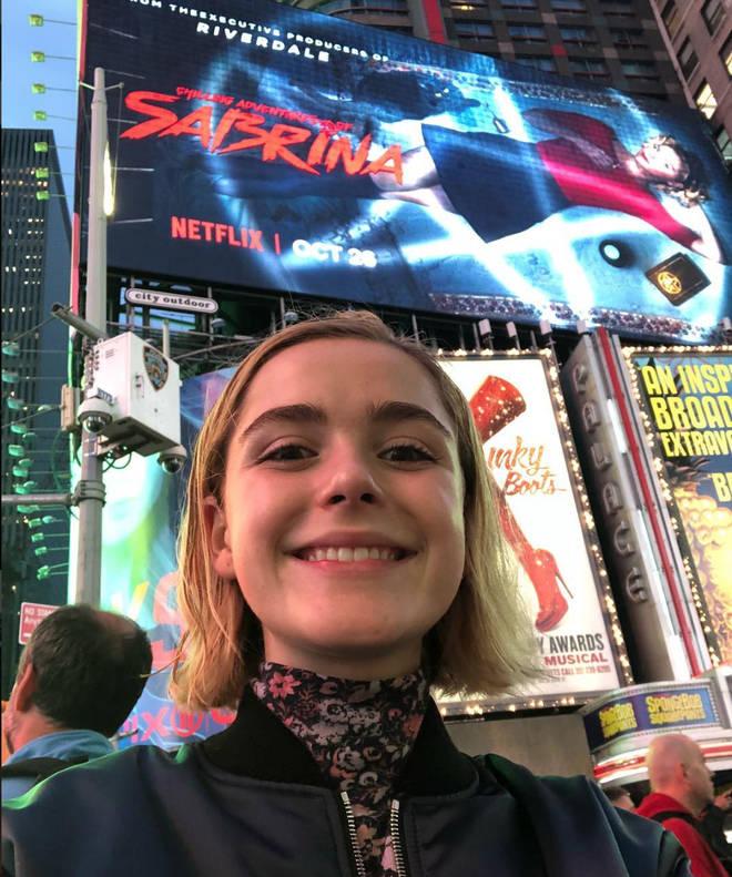 Kiernan Shipka poses in front of Chilliing Adventures of Sabrina advert