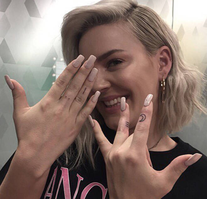 Anne-Marie has four different tatts on her fingers.