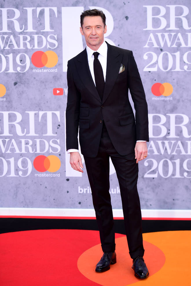 Hugh Jackman walks the 2019 BRITs red carpet in a tailored suit