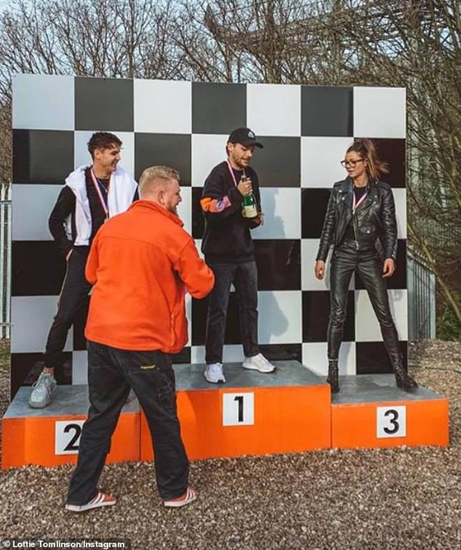 Louis Tomlinson on the winner's podium after go-kart racing